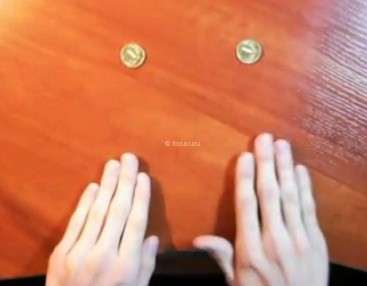 две монеты лежат на столе и руки фокусника готовы исполнить трюк