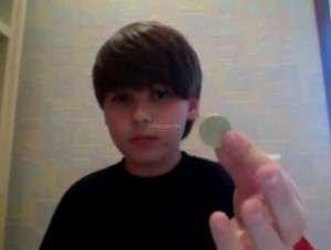 парень демонстрирует обычную монету перед самим фокусом