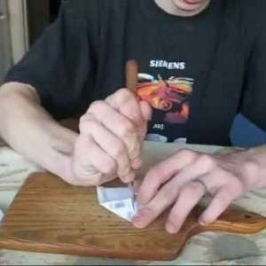 парень на доске разрезает купюру ножом и портит ее во время фокуса