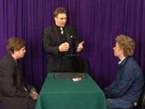 маг объясняет двум зрителям суть фокуса и он внимательно слушают