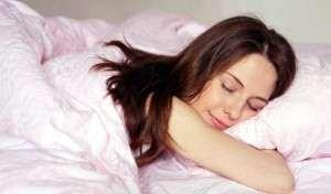 Улыбается и обнимает свою подушку